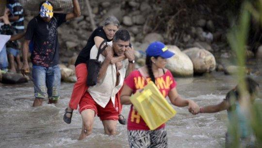 SAI Volunteer carries migrant woman on his back.