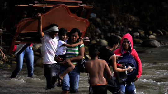 Venezuelan Refugees Crossing River into Colombia