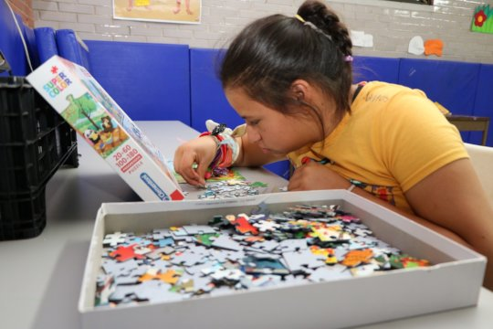 A girl highly concentrated resolving a puzzle