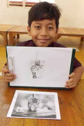 Student shows drawing he is working on