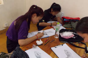Students practice drawings of dancer's hand