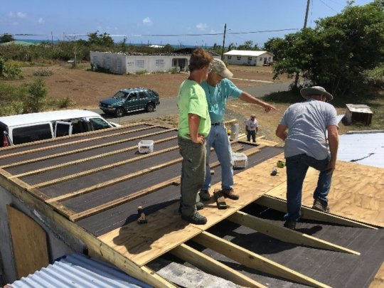 Members of the LTRG providing roofing to a family
