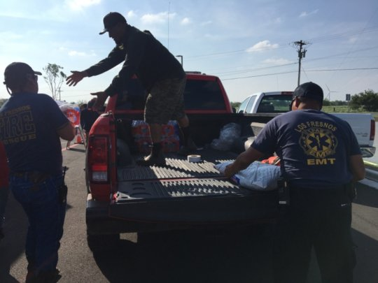Local officials help with water distribution.