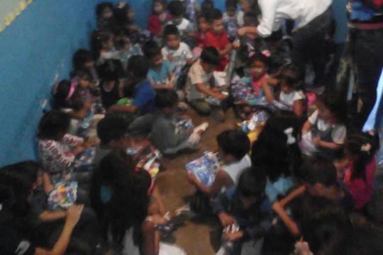 Children opening Christimas gifts at the Event
