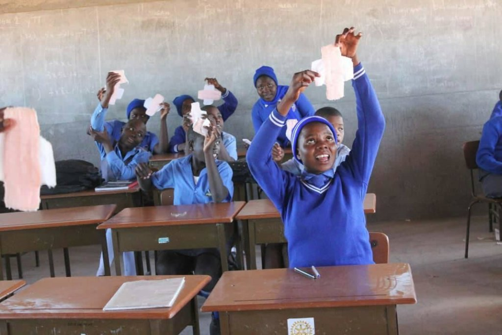 Girls showing off the reusable pads they made