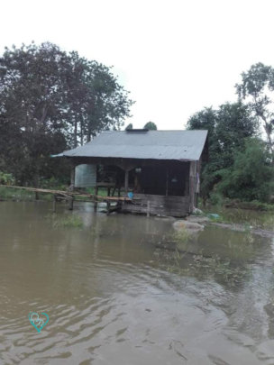 A small hut in the middle of a flooded field.
