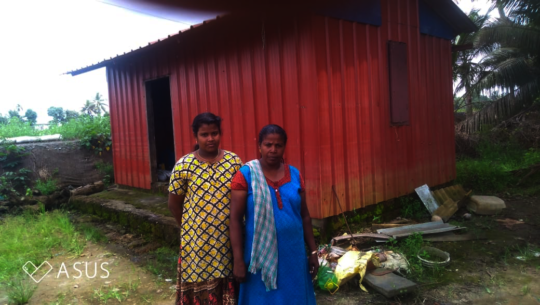 Maya with her mother in front of their house
