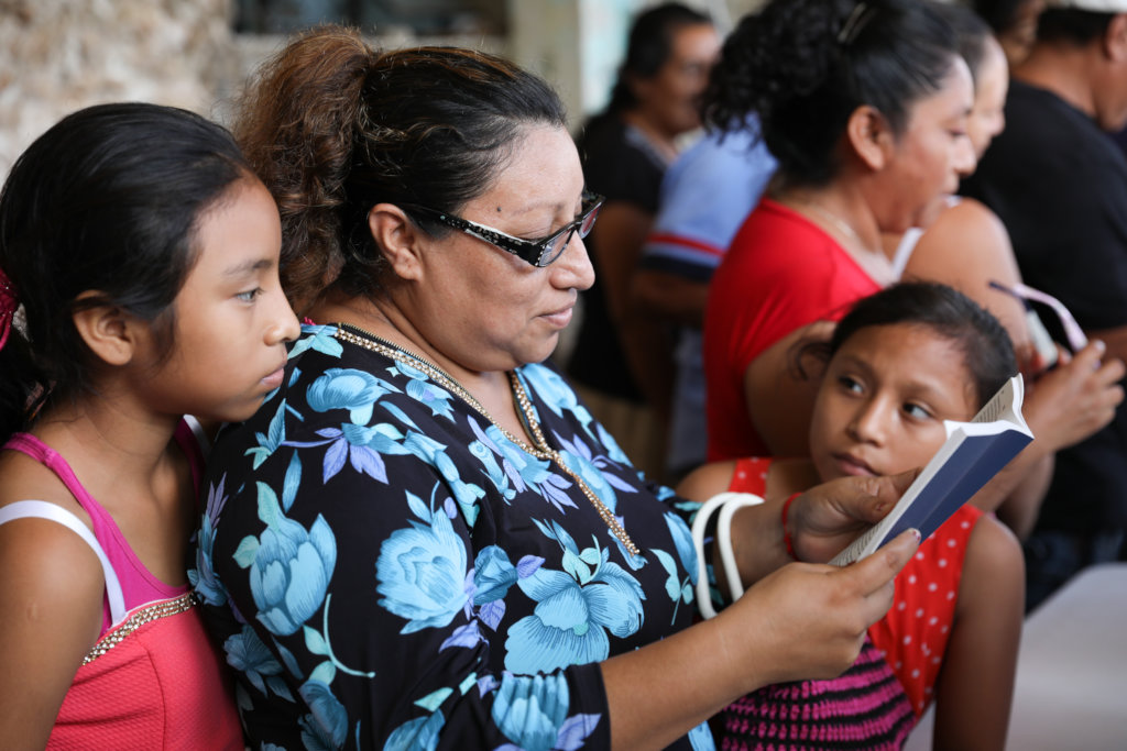 Mother w/daughters reads with new glasses: Mexico