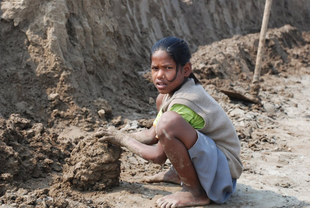A young girl molds bricks in the sweltering Indian sun