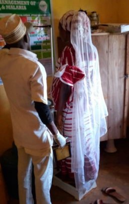 Health worker checking weight of a pregnant woman