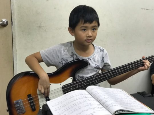 The second grade boy playing bass intently