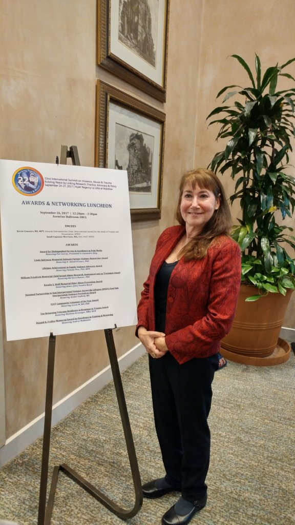 Pamela J Pine in front of IVAT Awards Poster