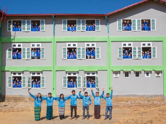 Staff team with students and school building