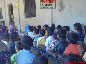 Balwadi Teacher teaching Pray to children