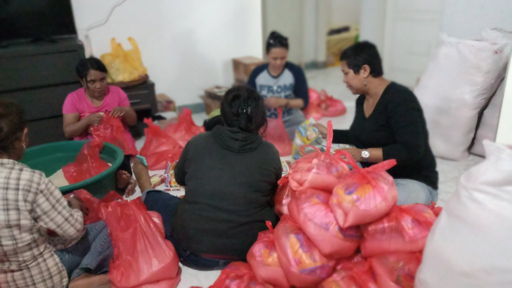 Preparing food packages with local volunteers