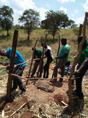 CHWs constructing pit latrine for a poor family.