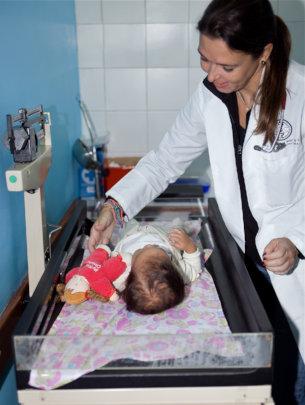 Pediatrician checks baby's weight