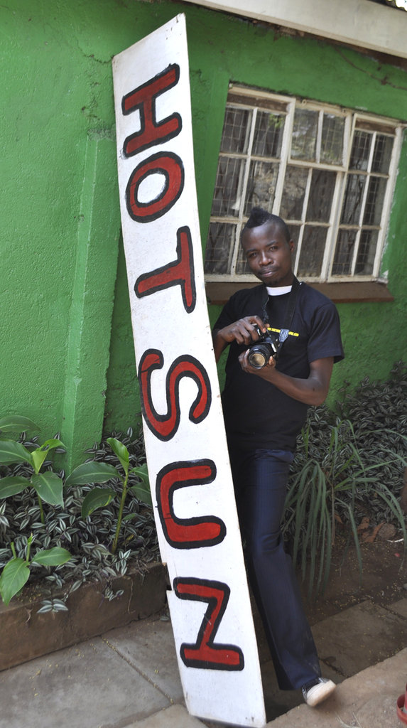 Ronald Omondi with camera & Hot Sun sign
