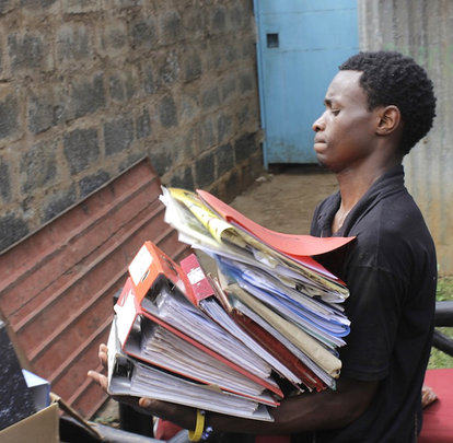 Kibera Film School trainee moving files
