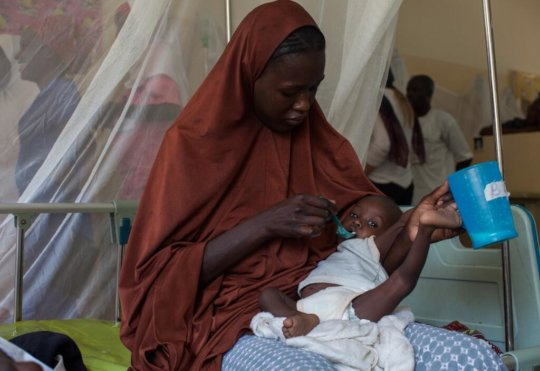 A Nigerian mother gives her child fortified food.