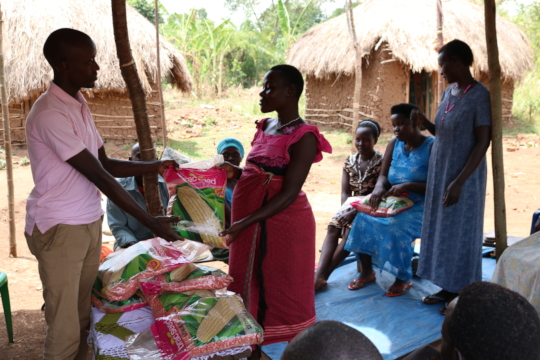 Project leader distributing seeds to a beneficiary