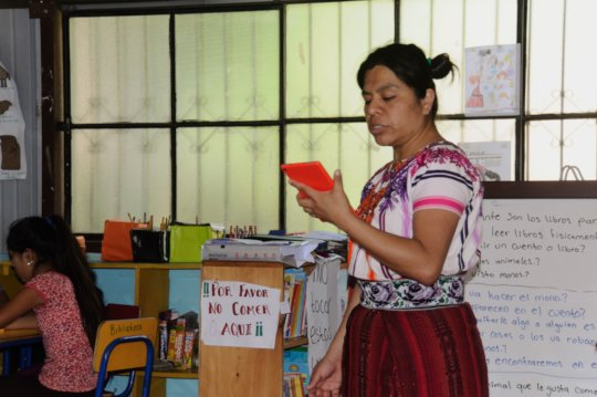 Lidia reads a story aloud using a tablet