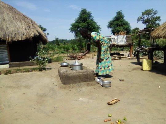 A refugee cooks on an energy saving stove