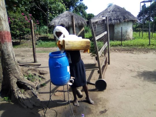 Filling the water stand for handwashing