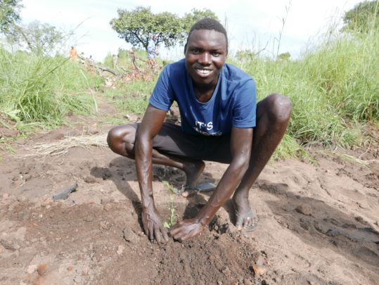 Young refugee plants a Combretum molle seedling