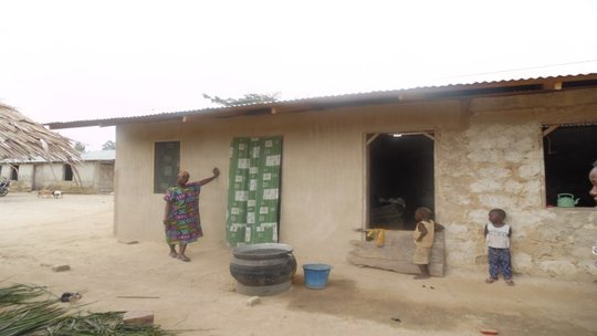 Ayishetu in front of her partly completed house
