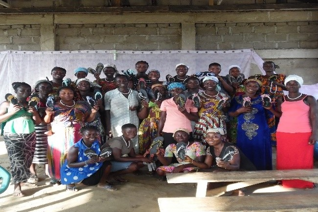 group of women show their newly-made beaded sandals