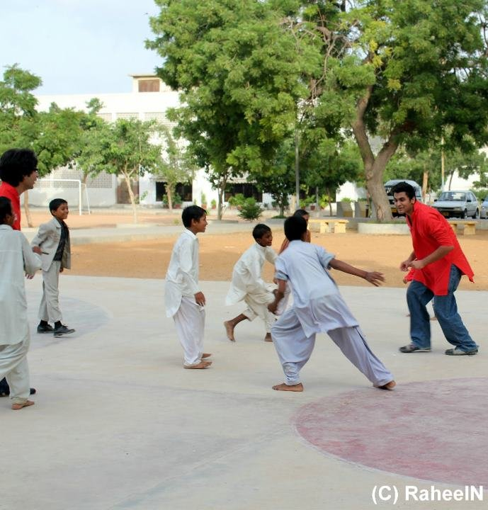A volunteer teaches the students basketball