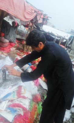 Sher Ali collecting trash at the local market