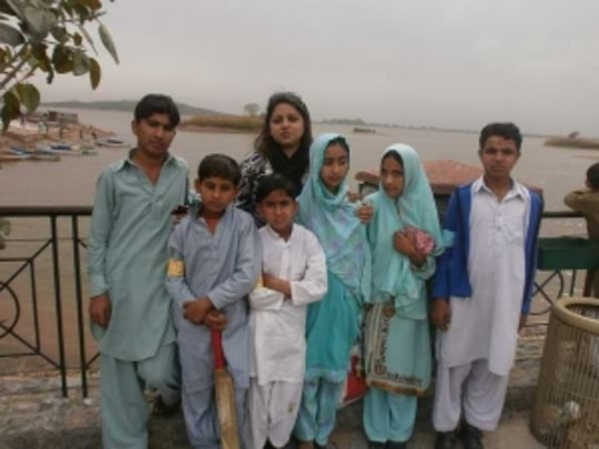 students, cricket bat in hand, pose by the lake