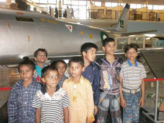 Children pose by a jet at the museum