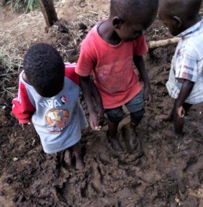 Kids stomping mud for TAKATAKA House