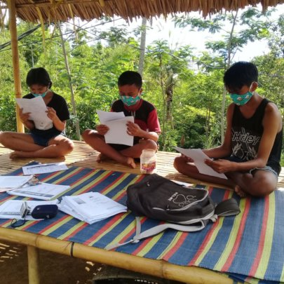 Students taking exam at home supervised by teacher