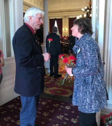 Julia Hampton (VT-SPC) hands flower to legislator