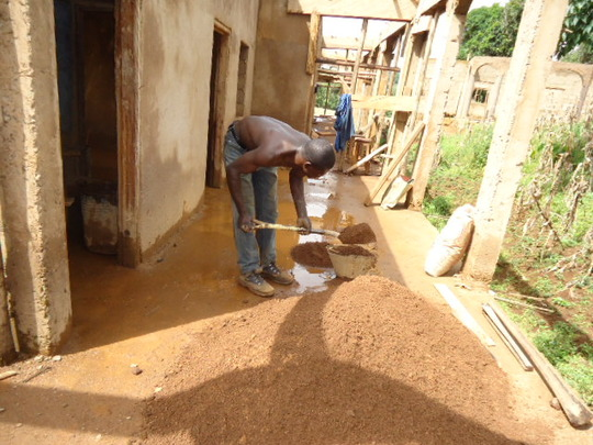 Bricklayer measuring sand to be mixed with cement