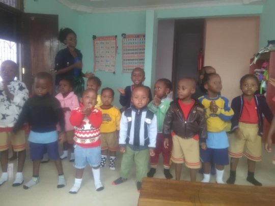 Lois singing with her nursery school students