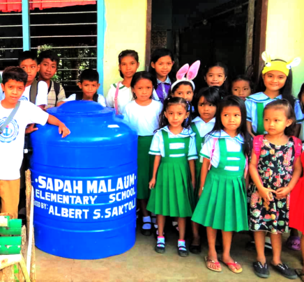 Students gathered around AAI clean water tank