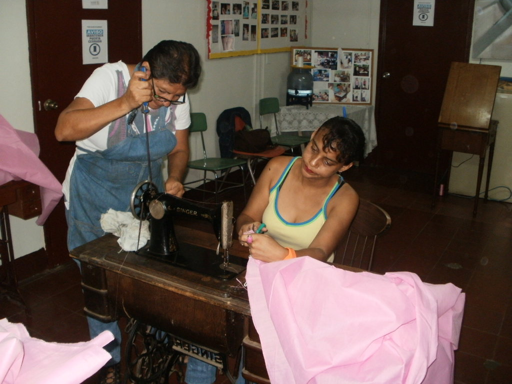 Sandra keeps machines working, Janina sewing