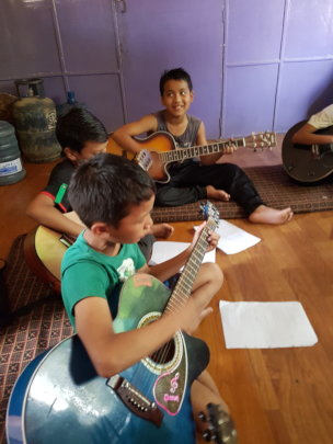 Playing the guitar, taught at School+Plus
