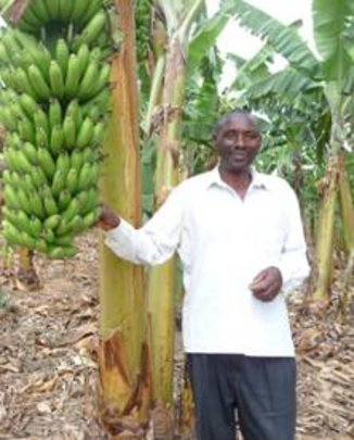 Matthew Bamwanga by a garden