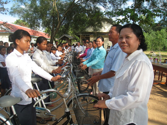 Roeun Sonang, left, receives her bike