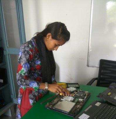 Indu working on repairing a laptop