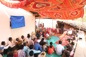 Villagers sitting under Manju's tent setup