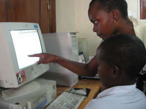 Student with instructor at AfricAid computer
