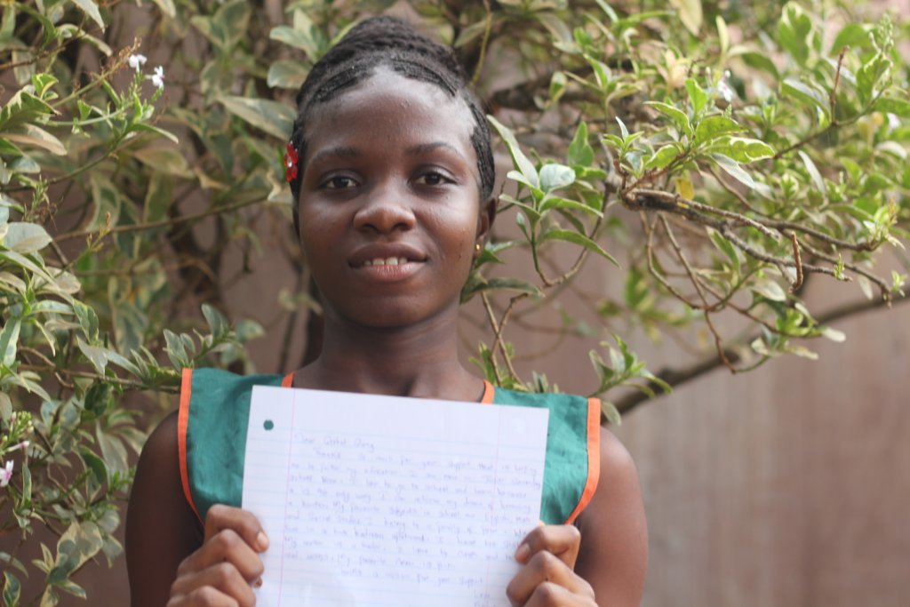 Kadiatu holding her Thank You letter