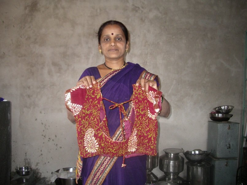 Holding a blouse that she has sewn